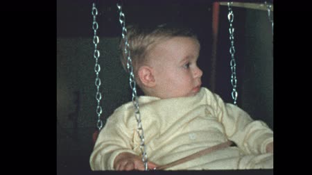 filmes : 1 year old baby boy swings on antique baby swing 1953