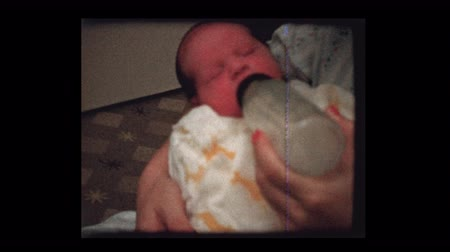 bottle feeding : Mother feeds newborn baby bottle of milk 1959 Stock Footage