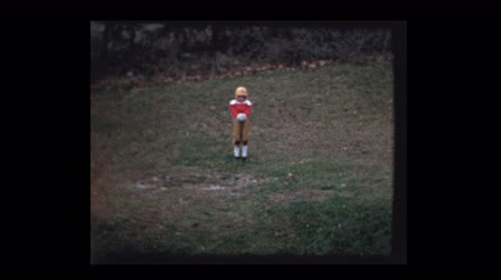 pré histórico : Young boy in football uniform punts football 1956