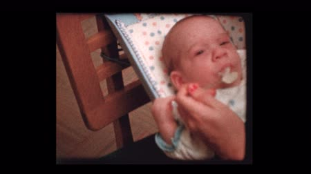 annelik : Infant eats baby food for first time 1959 Stok Video