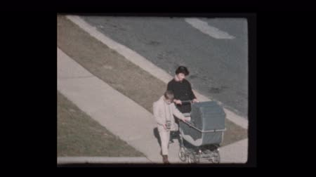Brother and sister take baby for walk in antique stroller 1959 Dostupné videozáznamy
