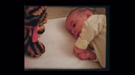 2 month old infant boy with stuffed animal in crib 1959