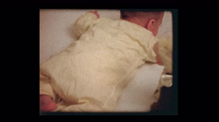 nostalgisch : 1959 2 month old infant boy laying on stomach tries to get up Stockvideo