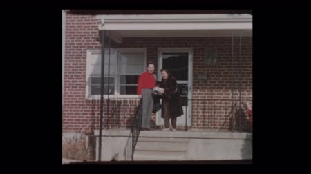 período : 50s Couple with woman in fur coat leave house 1955