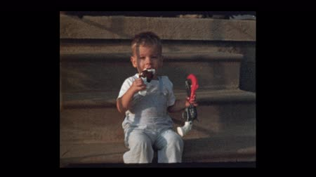 1953 Cute little boy eating ice cream on a stick holding toy gun