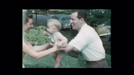 1953 Glamorous mom and dad toss baby boy with antique cars