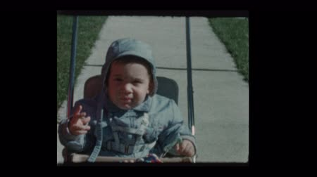 1960 Cute little boy in stroller plays to camera portrait