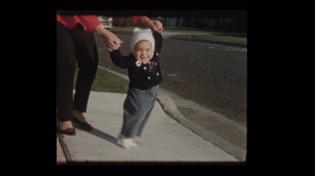 paternal : 1960 Mother teaching baby son to walk as antique car drives by Stock Footage