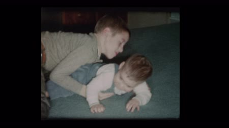 Little boy plays lovingly with baby brother 1960