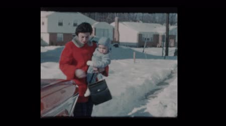 1960 Mom holds baby bundled up baby boy after snowstorm