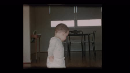 vándorlás : 1960 Curious Cute little boy wanders around living room