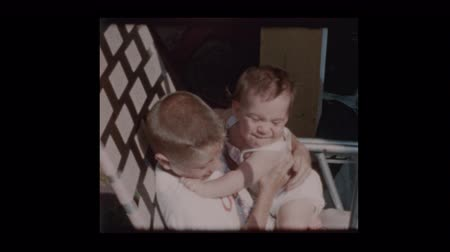 gyengéd : 7 year old boy holding baby brother in lawn chair 1961