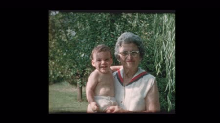cidadão idoso : Portrait of elderly grandmother holding baby grandson 1961 Vídeos
