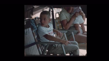 período : 1960 mother and baby boy hanging out with family in backyard