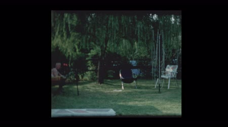 Grandfather hanging in hammock with family in suburban backyard 1961
