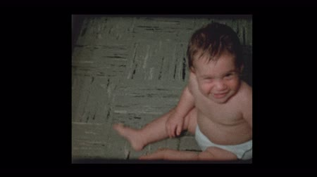 film camera : Cute little boy in diapers crawling around plays to camera 1960