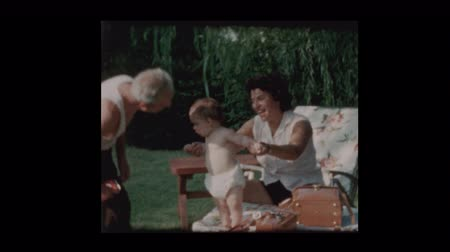 omini : Grandfather kisses baby grandsons belly 1960 Filmati Stock