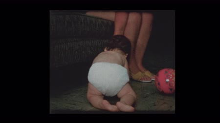 Mother give baby boy in diapers a coaster to play with 1960
