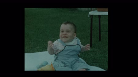 szentimentális : Smiling happy baby sitting on lawn outside 1960