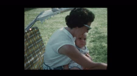 1959 Mom feeds baby sitting outside on lawn chair 1959 Стоковые видеозаписи