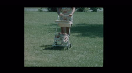 bonding : 1960 Woman pushes baby in antique stroller through the grass