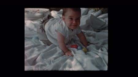 alcançando : 1960 Happy baby boy crawling and sitting on blanket outside