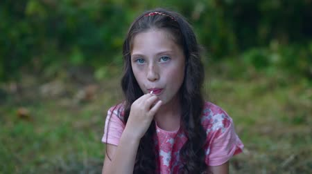 леденец : Beautiful little girl eating a lollipop candy in the garden. Стоковые видеозаписи