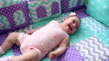 cobertor : Beautiful little girl lying in a cot in the room and laughs