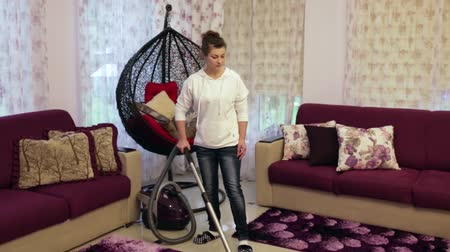 temizleme maddesi : Young beautiful woman cleans the house. Hoover carpet Stok Video