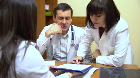 clínico : A group of doctors talking. Two women and a man. Look in the folder with the documents. Stock Footage