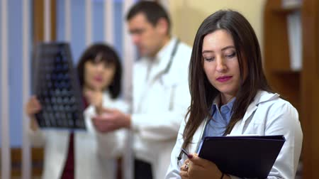 сотрудники : Female doctor holding a folder in his hands. In the background, the doctors checked the x-rays. Стоковые видеозаписи