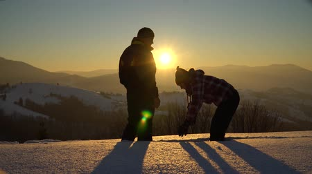jumped : Tourists a man and a woman in winter on a snow-covered mountain toss snow up. They jumped gaily, holding hands. In the background, the sun sets over the mountain.