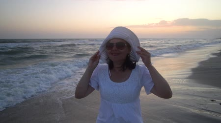 plage : Young beautiful woman is standing by the sea at sunset. In a white dress and a white hat. She looks at the camera and smiles. Stock Footage