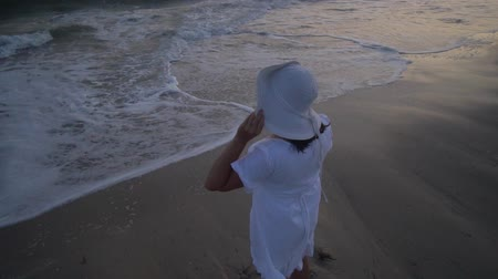 plage : Young beautiful woman is standing by the sea at sunset. In a white dress and a white hat. She stands on the shore and looks into the distance.