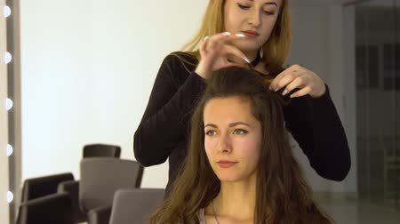 kuaför : Young beautiful girl in beauty salon. Hairdresser-stylist makes the girls hair. The hairdresser curls the hair with a styler and stacks them. Stok Video
