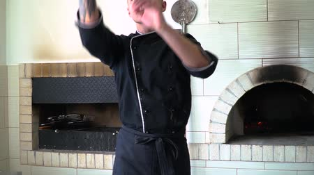 hamur : A young pizza maker prepares pizza in the kitchen of the restaurant. The cook rotates the dough in the air and spreads it on the table. Prepares black pizza. Slow motion.