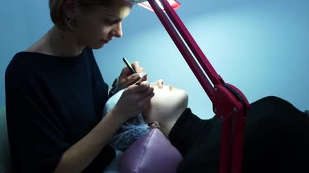 yanliŞ : Eyelash extension. Master make-up artist extends eyelashes to a young girl. The girl is lying down. A lamp is next to it.