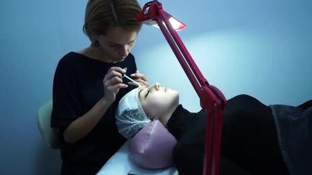 yanlış : Eyelash extension. Master make-up artist extends eyelashes to a young girl. The girl is lying down. A lamp is next to it.