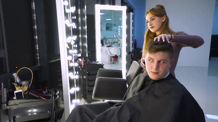 kuaför : A young handsome guy in a beauty salon. The guy is sitting in the armchair. The hairdresser cuts her hair. The guy is sitting in front of the mirror. He is pleased.