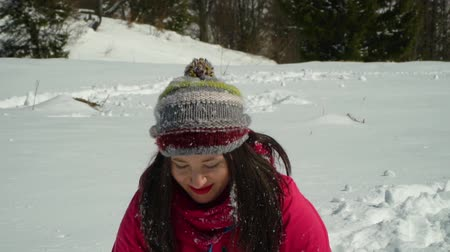 caráter : Happy young woman having fun throwing snow. She is laughing. A girl is walking in the winter forest on nature in the mountains. Slow motion.