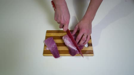 prancha : Kitchen. Close-up. A young woman is preparing food. Hands of the girl close-up. A woman is cutting fresh raw meat.