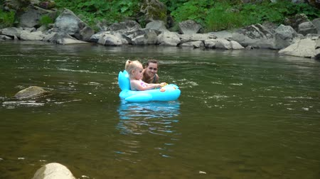 Mom and daughter in the river. A young beautiful woman is bathing in a mountain river with her little daughter. They are having fun and laughing. The girl is floating on an inflatable circle. Vídeos