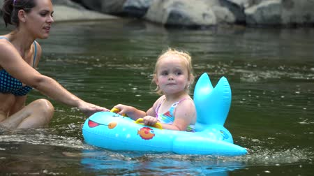 купаться : Mom and daughter in the river. A young beautiful woman is bathing in a mountain river with her little daughter. They are having fun and laughing. The girl is floating on an inflatable circle. Стоковые видеозаписи