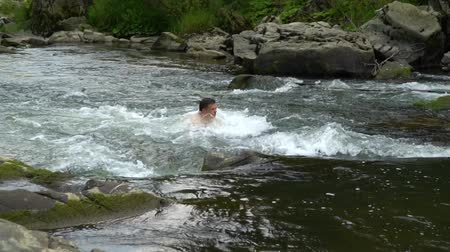 купаться : The guy is swimming in the river. A young cute guy bathes in a clean mountain river. He is happy.