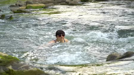 купание : Woman bathing in the river. A young nice woman is bathed in a clean mountain river. She is happy.