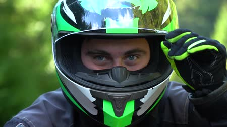 A guy on a motorcycle. Young handsome guy with his motorcycle in the mountains. The guy is looking at the camera. Close-up. Slow motion.