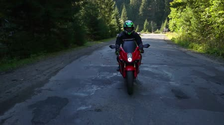 skútr : A guy on a motorcycle. Young handsome guy rides a motorcycle on a mountain road.