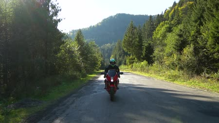 A guy on a motorcycle. Young handsome guy rides a motorcycle on a mountain road.
