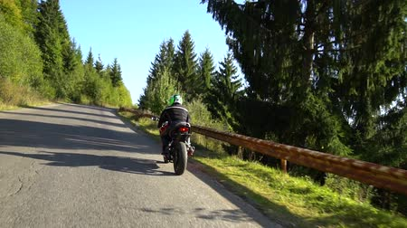 rider : A guy on a motorcycle. Young handsome guy rides a motorcycle on a mountain road.