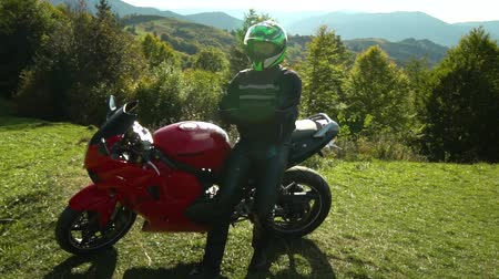 rider : A guy on a motorcycle. Young handsome guy with his motorcycle in the mountains. The guy stands near his motorcycle and looks at the mountains. He is happy.